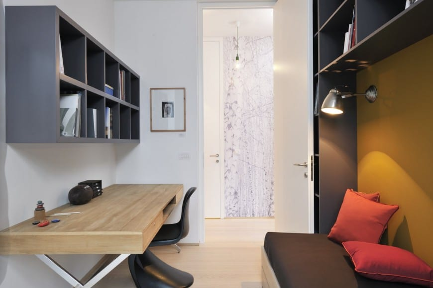 Small Industrial-style galley home office with grey built-in bookcases, minimalist chair and a table with a wide tabletop surface, and built-in seating with throw pillows and ambient wall lighting.