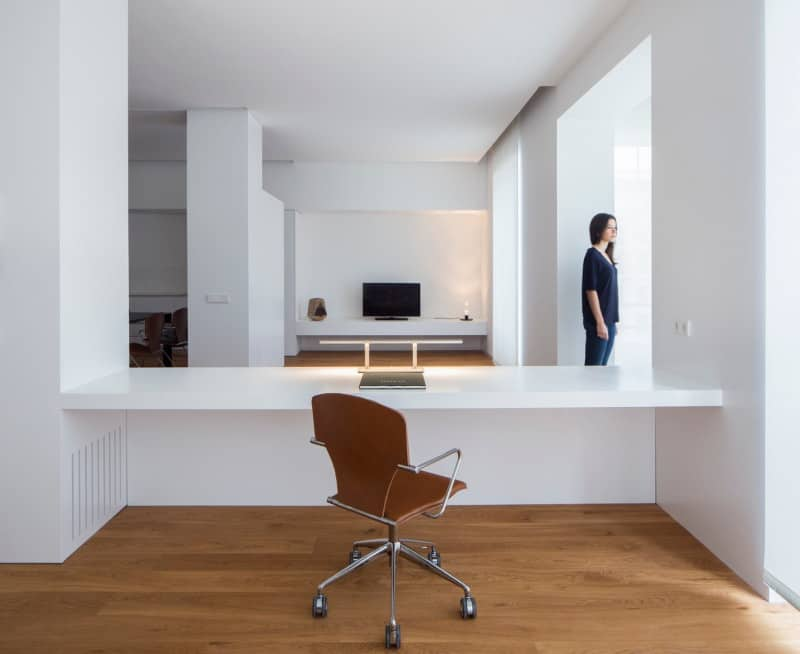 Woman standing outside the space alloted for a small open office in an open concept home.
