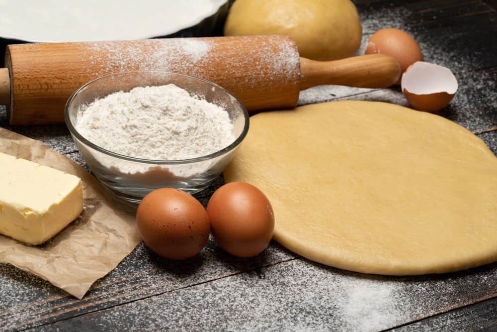 Rolling pin, flour, dough, eggs, and butter on wooden desk.