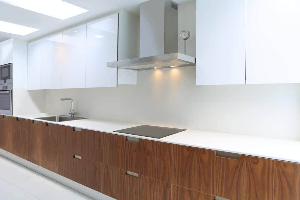 Walnut cabinets in modern white kitchen