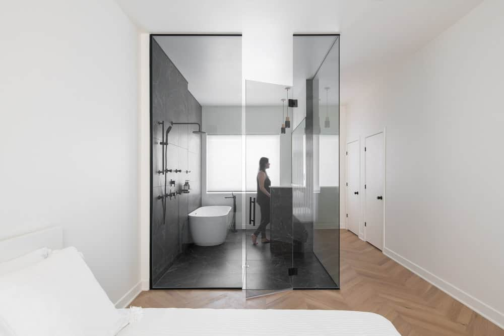 This is a close look at the modern bedroom that has a white bed that blends with the white walls and white ceiling. These are complemented by the glass-enclosed bathroom on the side of the bed area.