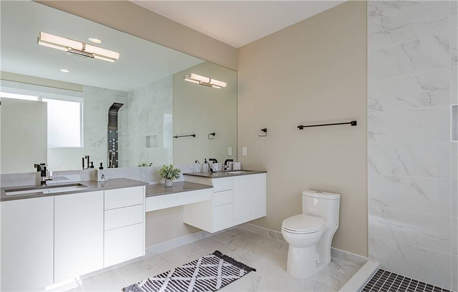 This primary bathroom features a floating double sink vanity and a sleek shower area reflected in the massive mirror. Marble tile walls and backsplash add elegant touch to the room.