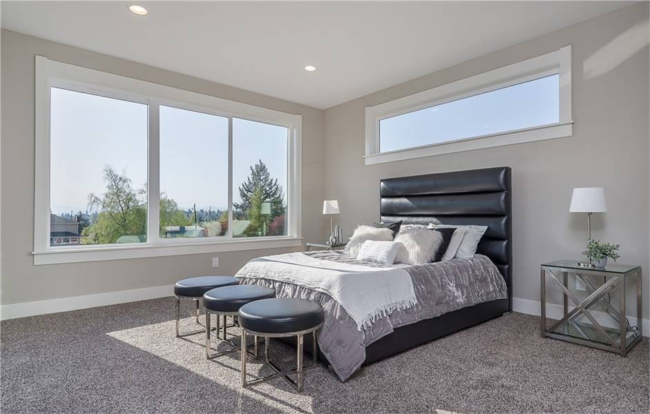 Primary bedroom furnished with mirrored nightstands, black leather bed, and matching round stools. Picture windows frame the surrounding views as they bring ample natural light in.