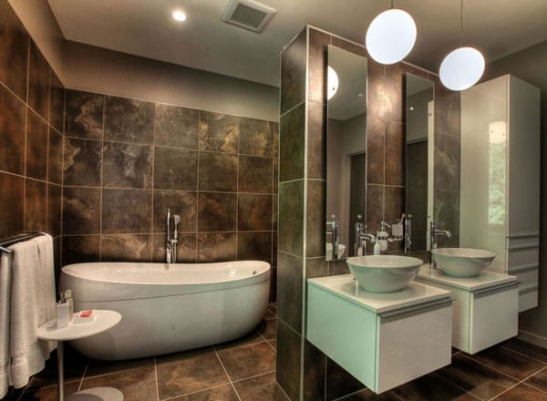 This primary bathroom has a dark marble tone to its floor tiles that extend to the walls. This makes the white freestanding bathtub and the floating sinks stand out.