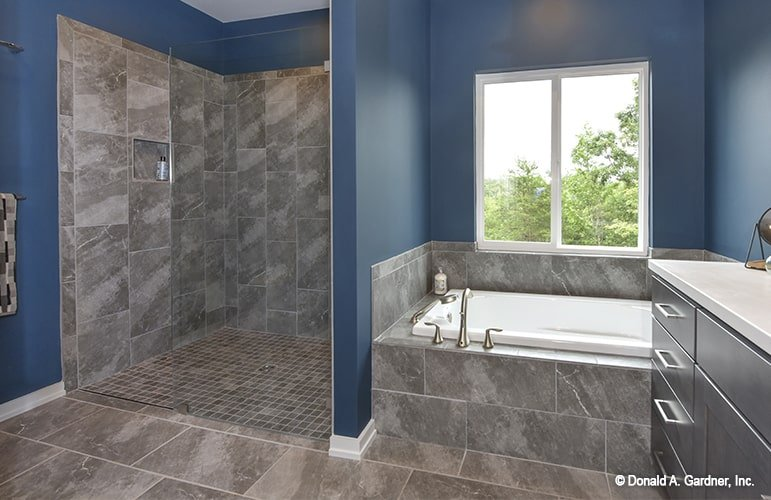 Primary bathroom with dark blue walls and tiled flooring that's mirrored on the tub surround and shower backsplash.