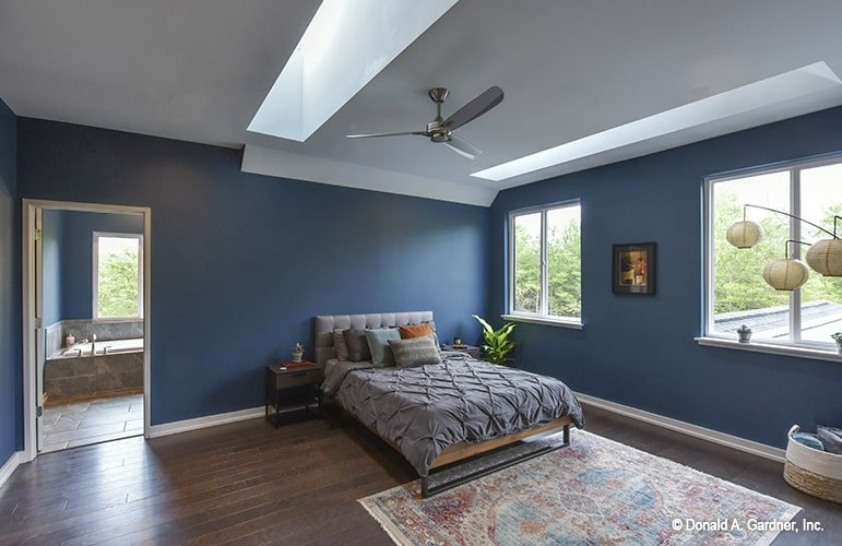 Dark blue walls create a serene vibe in this primary bedroom. It is well-lit by natural light coming in from the white-framed windows and sleek skylights.