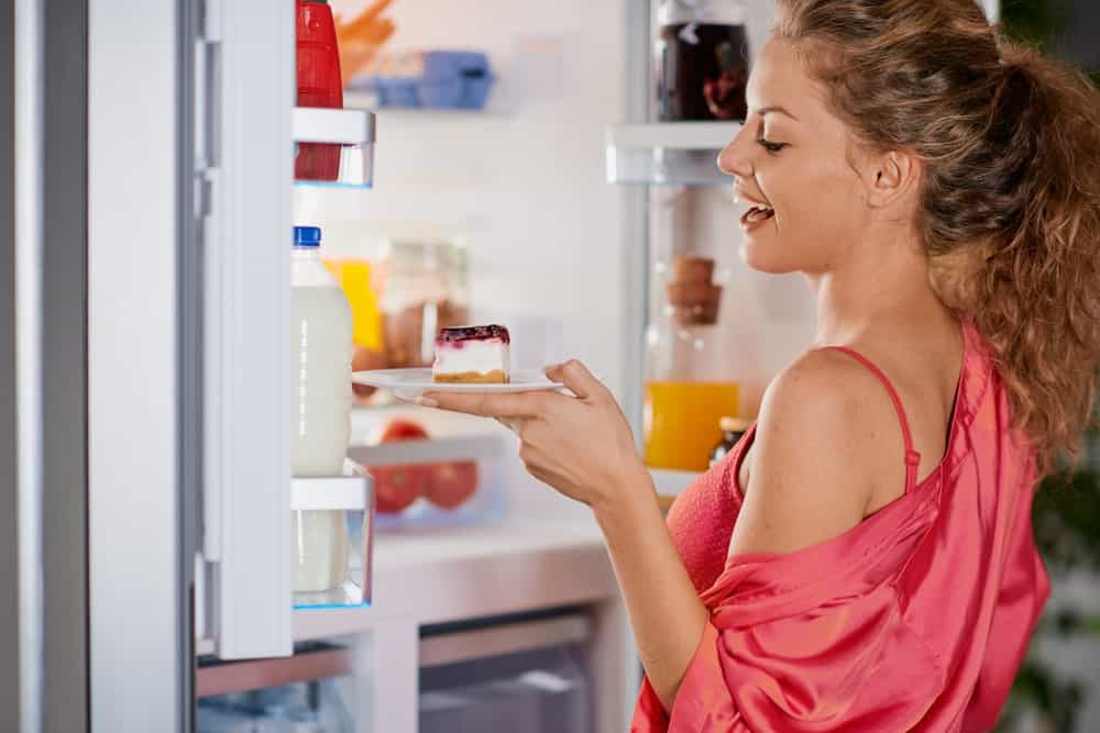 A woman taking a piece of strawberry cheesecake out of the fridge