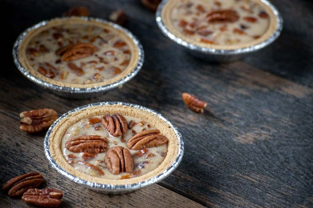 Pecan tarts and nuts on wooden desk.