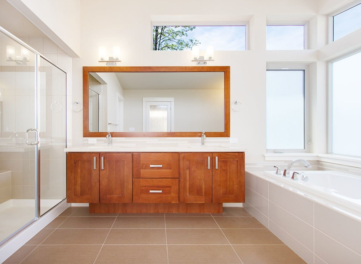 Framed mirror and wooden cabinets of the double sink vanity break the monotonous white scheme of this primary bathroom.