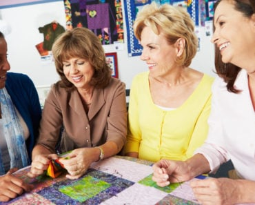 Four women working on a quilt