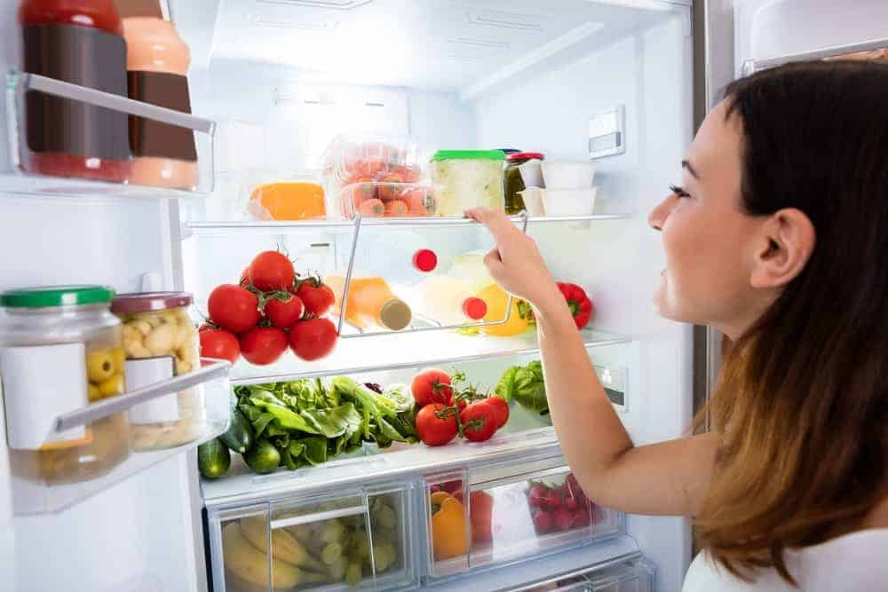Woman inspecting food in a fridge.