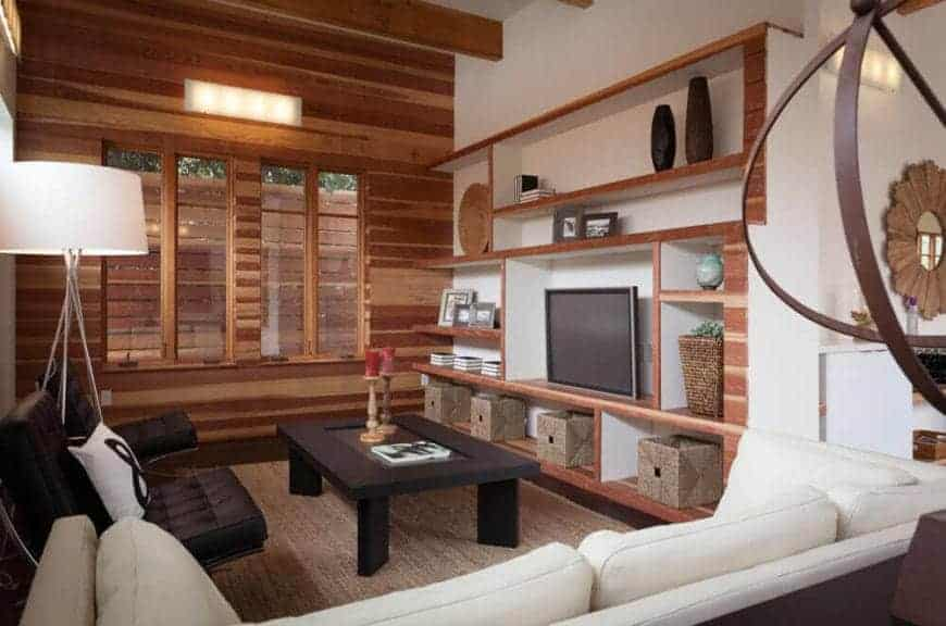 A small but cozy living room because of its wooden elements. It features custom built-in shelves, a dark wooden, glass top coffee table over a brown rug, white sofa, a pair of black lounge chairs and a huge floor lamp that creates a soft, cozy atmosphere to the room.