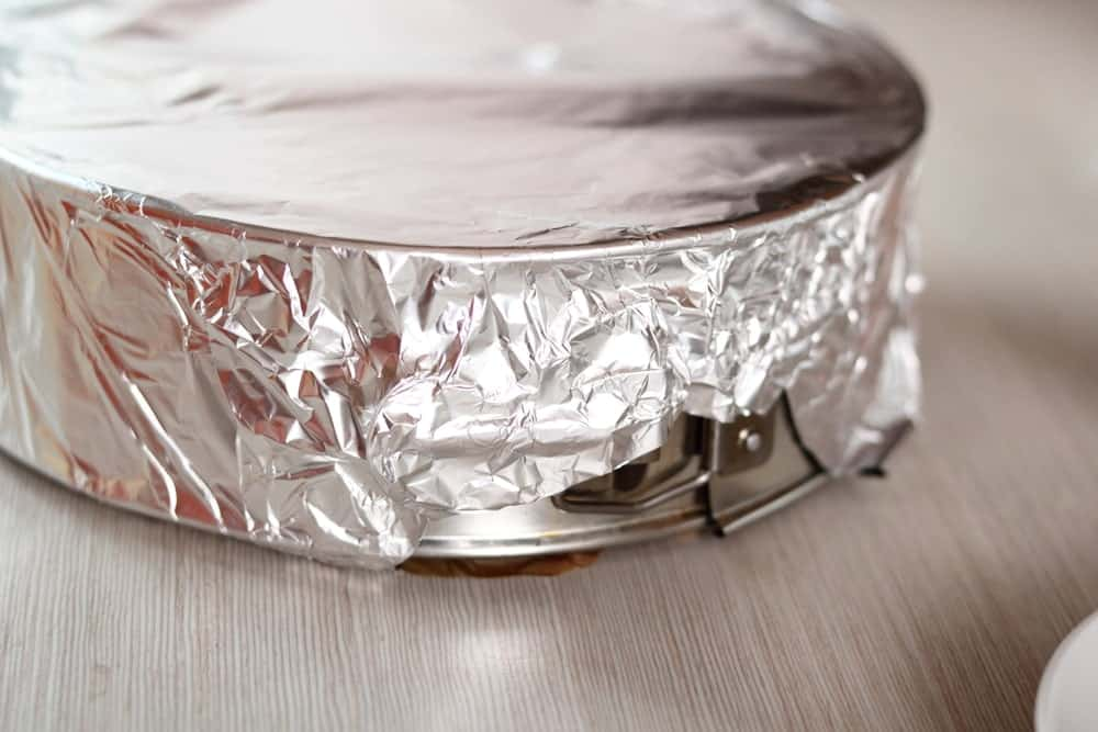 Wrapping pecan pie in an aluminum foil.