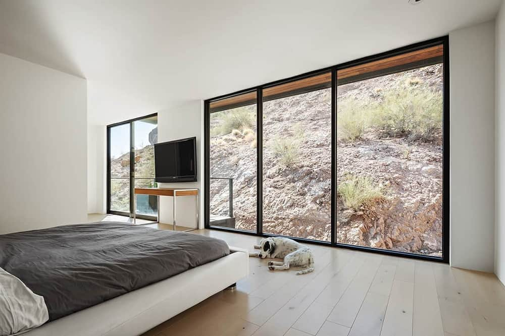 This is a full view of the modern and minimalist bedroom that has a white bed in the middle of the hardwood flooring brightened by the glass walls.