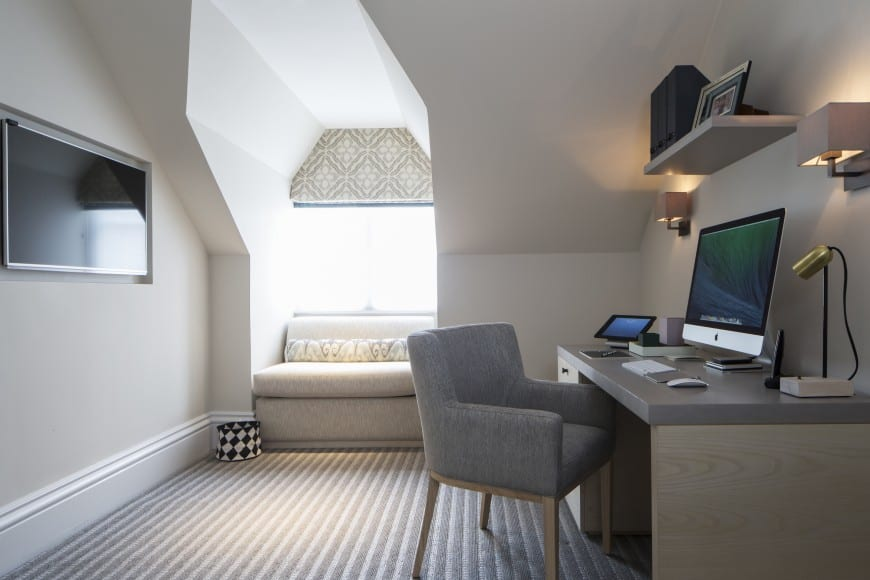 Attic home office with a window seating, a wall-mounted TV, carpet flooring, and a floating shelf above the office table and chair.