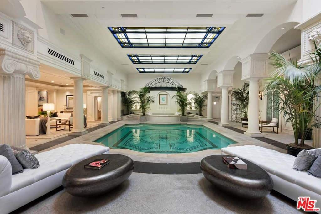 This grand indoor pool is nothing short of magnificent and lavish. It is right in the middle of the house with tall and elegant white pillars at either side, relaxing chairs at both ends and a number of fresh, green planters surrounding the pool.