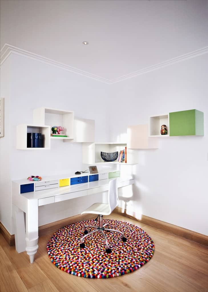 Small white modern home office with cubbies shelving, built-in desk with storage organizers, and some colorful accessories for a jolt of color.