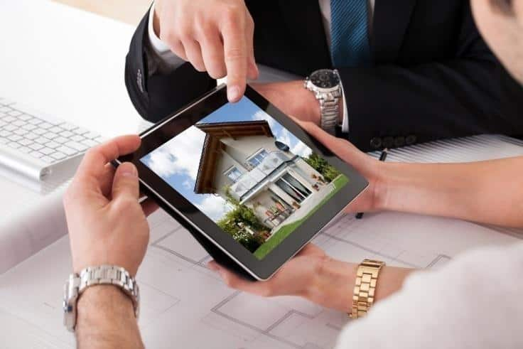 two people discussing the image of a house on a tablet