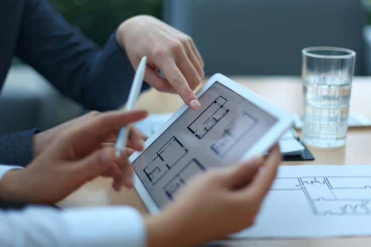 two people discussing architectural plans displayed on a white tablet