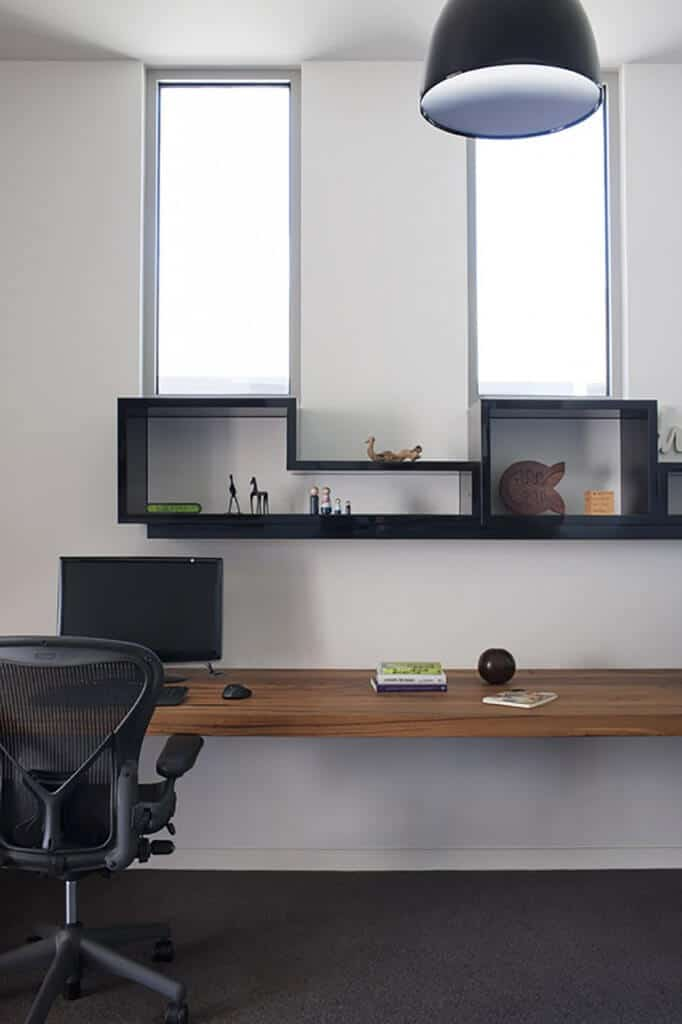 Home office with a clever bookcase or shelving design by the windows and a rectangular wood tabletop.