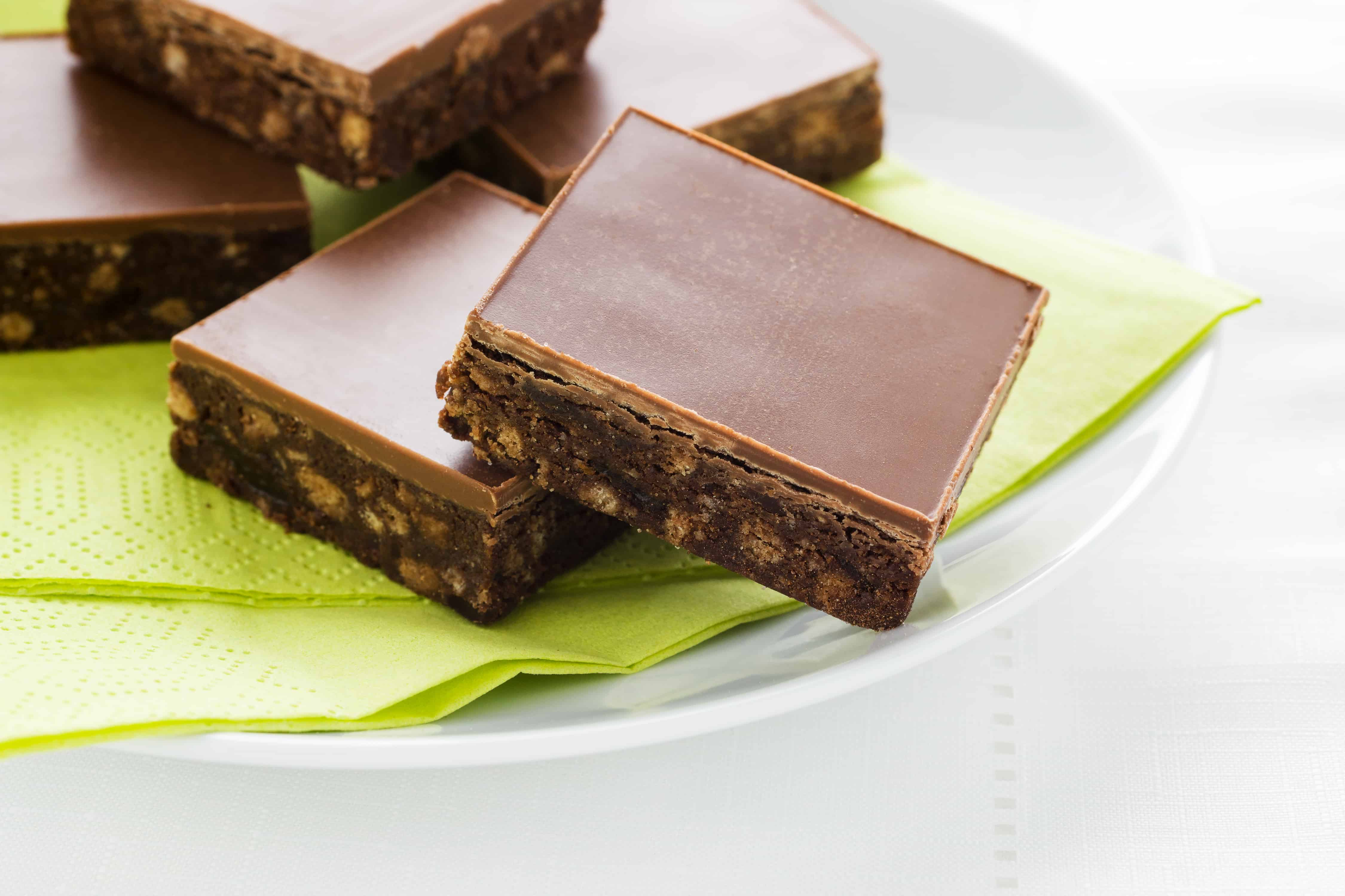 Chocolate fudge squares on a white plate and green napkin