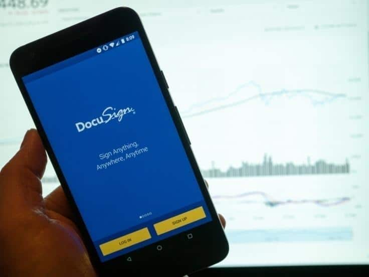 smartphone with DocuSign app open in front of computer screen with charts