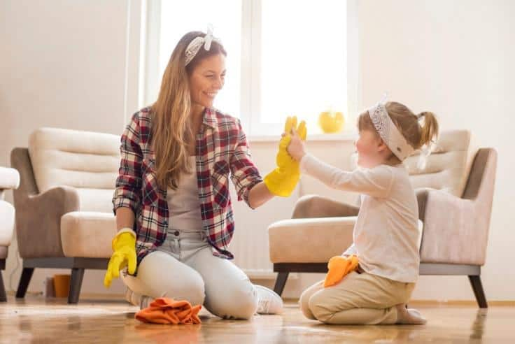 Mother and child smiling as they are cleaning and having fun