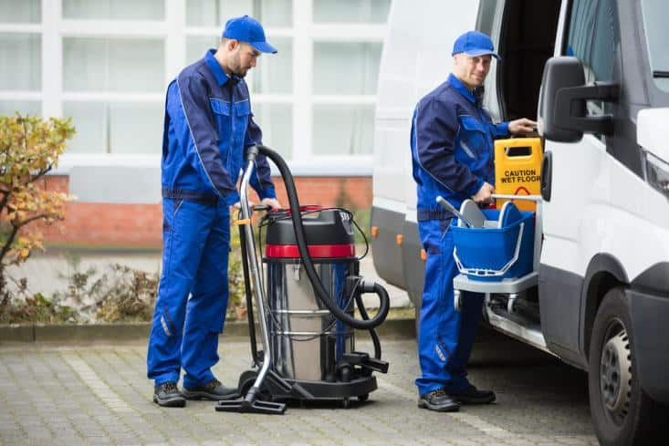 Two house cleaners unloading cleaning equipment from van