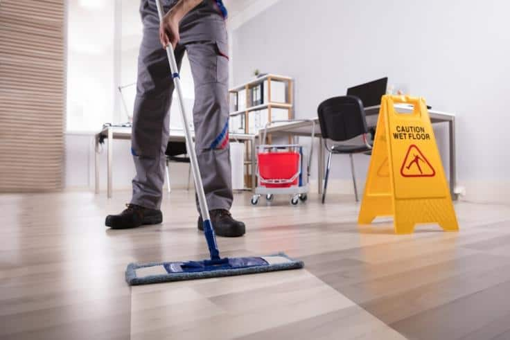 House cleaner mopping floor clean and yellow slippery floor sign on side