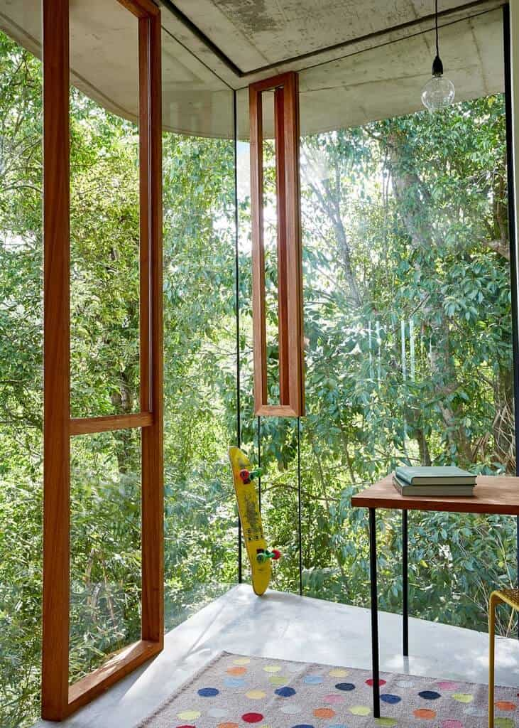 Contemporary home office with full glazed walls that let in the stunning greenery outdoors and some wooden rectangular frames for a touch of visual warmth to the room.