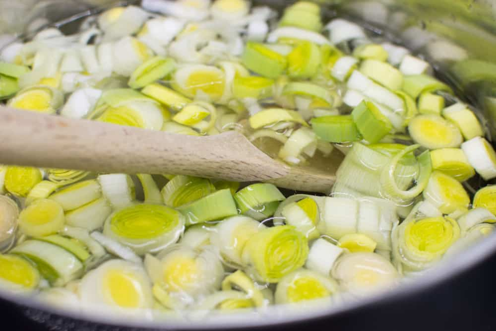 Leeks in olive oil in a pan witha wooden spoon