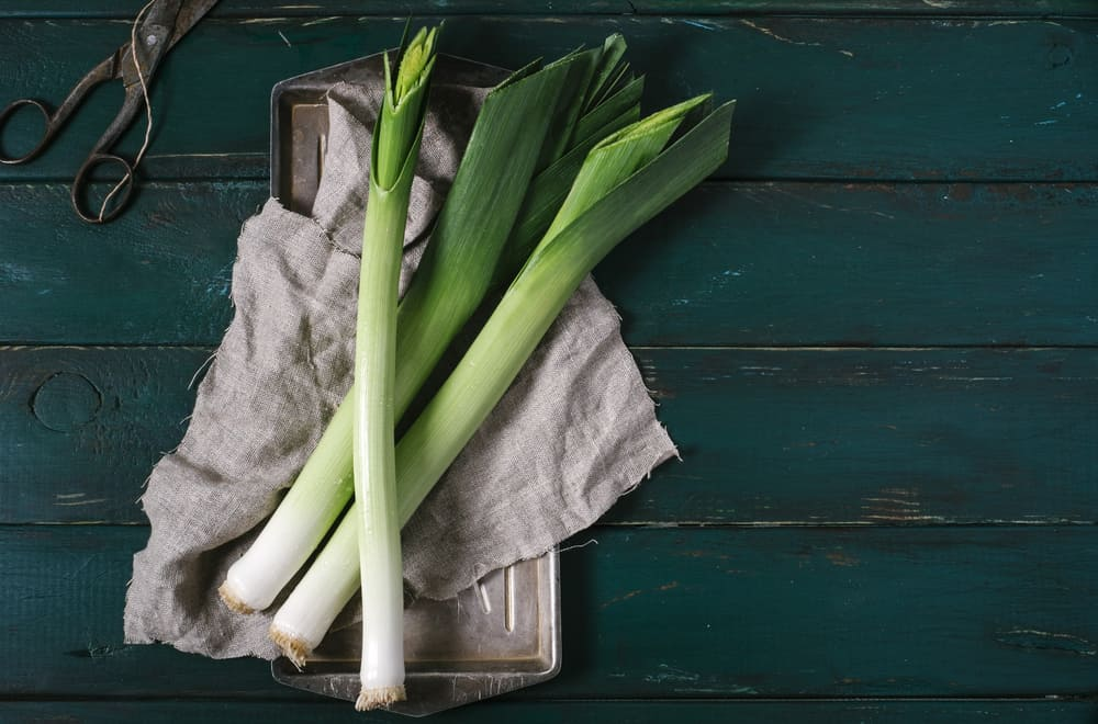 Leeks on a cloth placed on a green wooden table