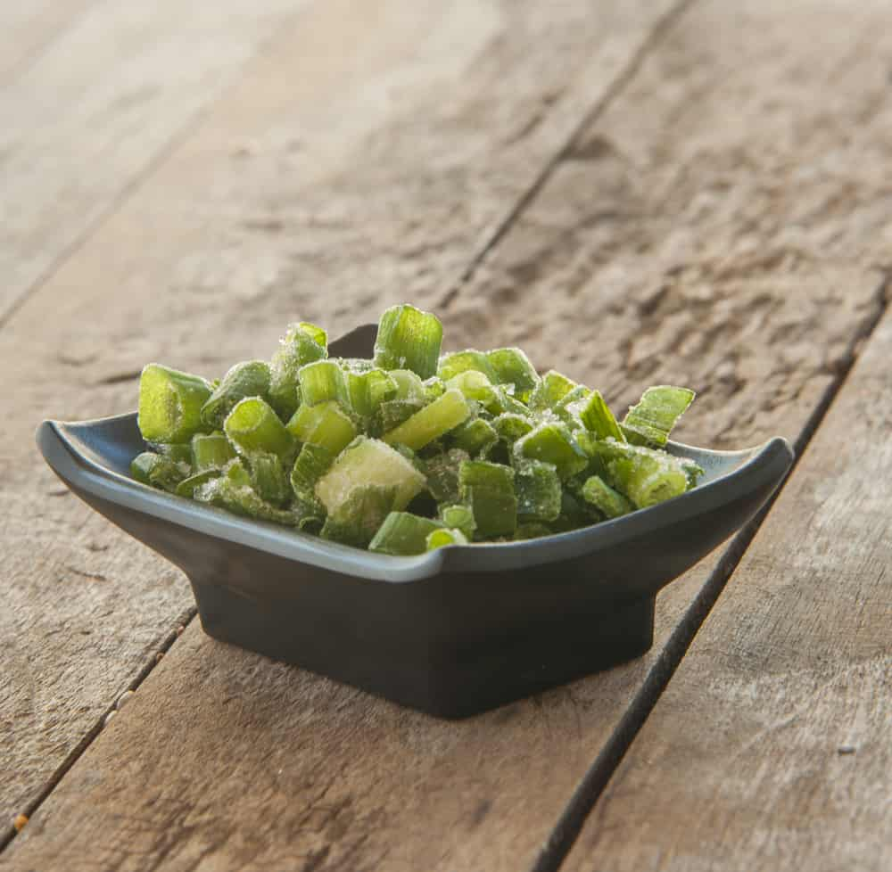 Chpped leeks in a black bowl on a wooden table