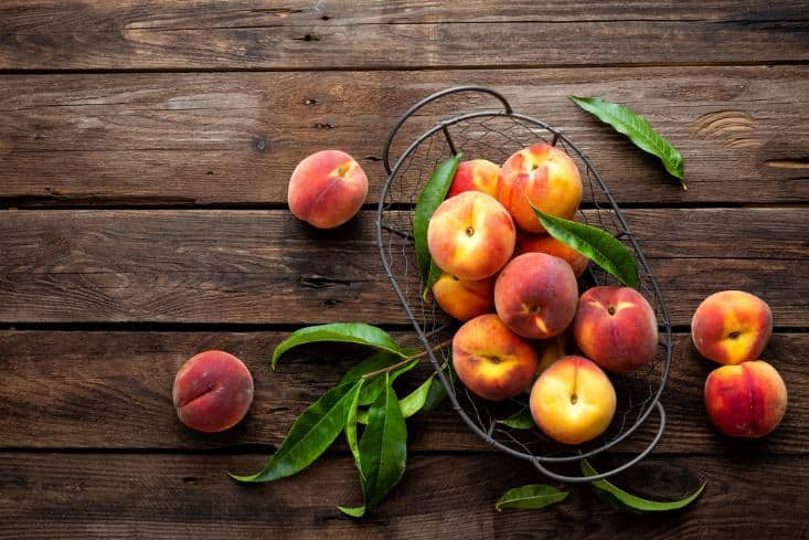 Nectarines in a steel basket on a table