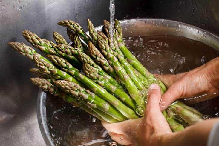 A man washing asparagus with water