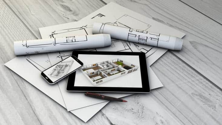 Showing Suite realtor software tool on tablet and smartphone placed on wooden table with architectural plans