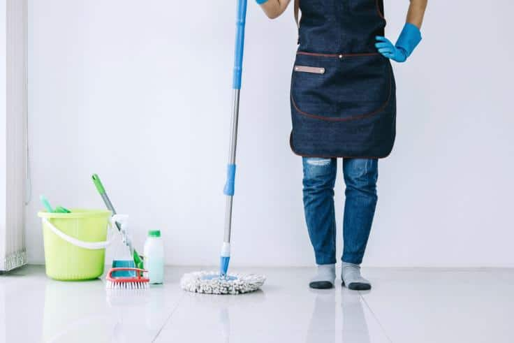 House cleaner wearing apron standing with mop on a reflective floor