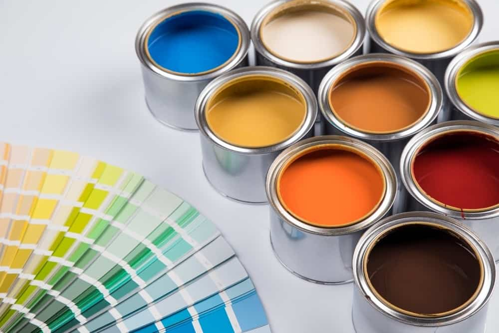 Open boxes of paint in front of color chart