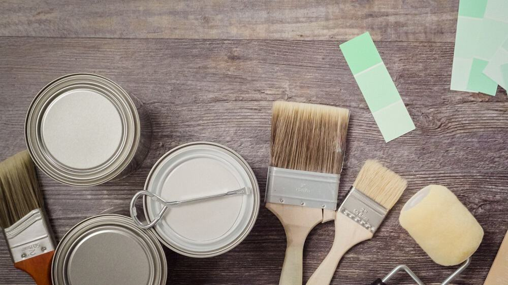 paint brushes and closedpaint can on brown wooden table