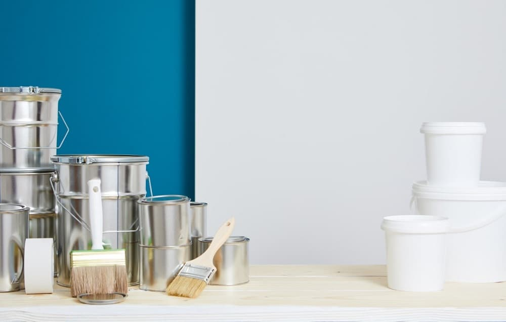 silver and white paint cans on wooden table