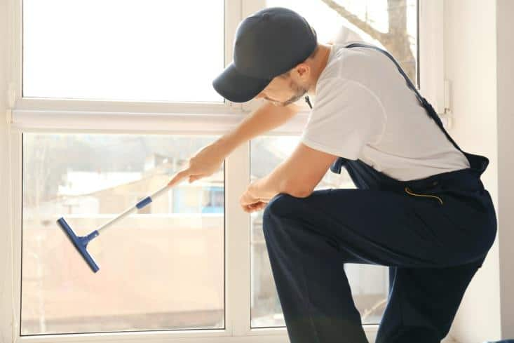 House cleaner wearing a black cap wiping the window from the inside