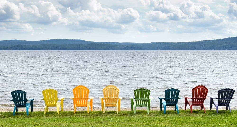 A row of colorful adirondack chairs placed at the waterfront.
