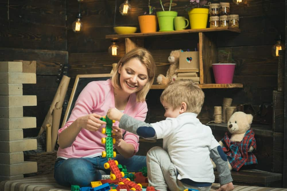 Mother and son playing Lego toys in the basement playroom.