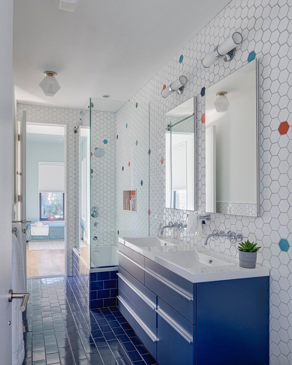 The walls of this bathroom have hexagonal tiles on the upper section of the bathroom with a few colorful tiles standing out in their isolation amongst white. The lower section is dominated by the bright blue tiles of the floor and the modern blue vanity.