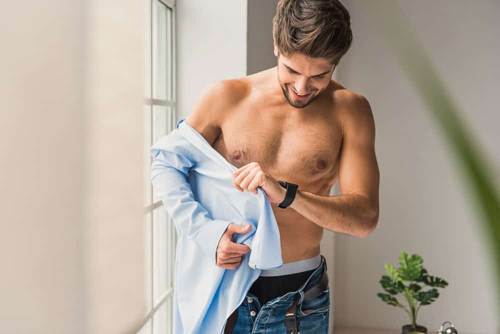 Young man putting on a long sleeves shirt.