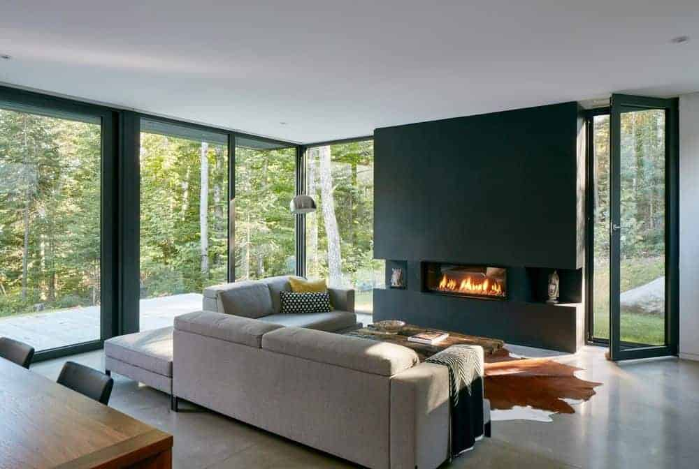 Living room with transparent glazed patio entry that lets you enjoy the peace and tranquility of the forest. It features a black accent wall mounted with a digital fireplace against a gray L-shaped sofa with a black throw blanket and pillows. A wooden coffee table sits on a rustic rug over a tiled floor.