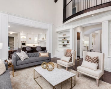 Stunning contemporary formal living room with white and gray furniture and very tall ceilings.