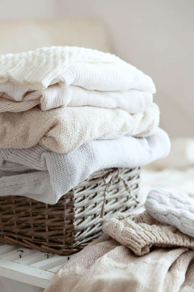 Folded sweaters in a basket