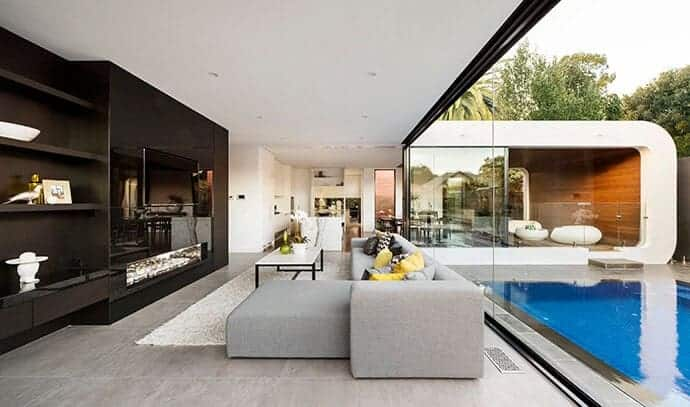 Single glazed frameless glass partitions provide a great view of the stunning pool on this modern living room. A gray sofa with chaise lounge faces the black built-in cabinet with shelves.