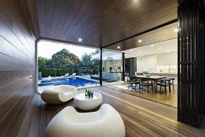 Minimalist living room covered with wooden panels from the ceiling to the walls and the flooring, accentuated by white modern chairs and a round coffee table and brightened by the natural light coming from the glass walls and recessed lighting.